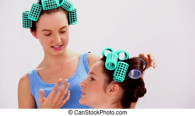 Girls in hair rollers and pajamas chatting at girls night in