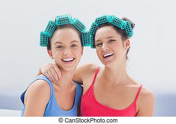 Girls in hair rollers and pajamas smiling at camera at girls...