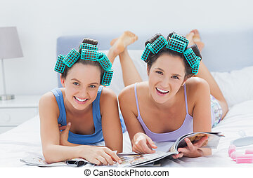 Girls in hair rollers holding magazines and smiling at...