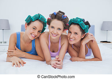 Girls in hair rollers lying in bed smiling and looking at...