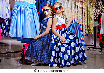 7b1e550c4942 Two little fashionable girls go shopping. Kid's fashion. Seasonal sale,  shopping. girls in pin-up dresses