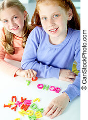 Portrait of smart girls making word ?school? and looking at camera