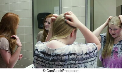 Girls in school restroom / bathroom - A few girls (students)...