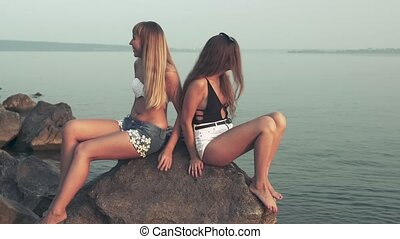 girls in swimsuits on the beach, sunset