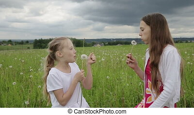 girls in the field blowing on dandelion in hand