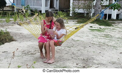 Girls in the hammock with the tablet on the beach