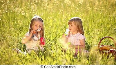 Girls in the meadow. Blow bubbles