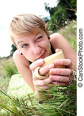 girls is drinking from a cup on a meadow