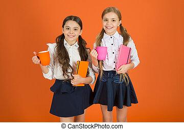 Girls kids school uniform orange background. Schoolgirl hold book or notepad and mug. School routine. Having break relax. Drinking tea while break. School mates relaxing with drink. Enjoy being pupil