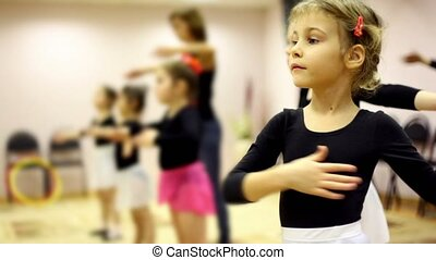 Girls learn how to dance with ballet teacher in recreation...