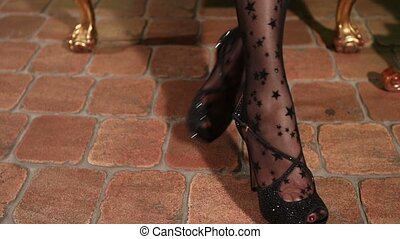 Girls legs in black stockings, the legs of the young girl in black lacy stockings, female legs in high-heeled shoes, stone floor, a chair, movement, the legs turn