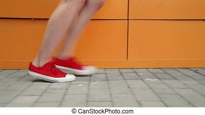 Girls Legs In red Trainers. Run Along The Orange Wall Ground...