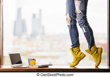 Girl's legs in yellow boots standing on windowsill with blank laptop screen, orange, coffee cup and notepads on blurry city background. Mock up