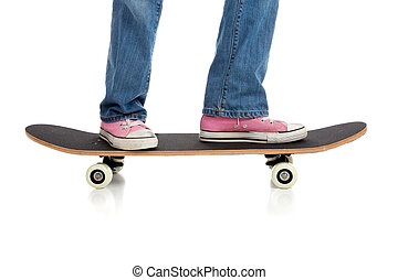 Girl\'s legs riding a skateboard on white