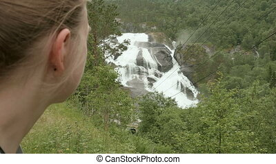 Girls look at waterfall in mountains