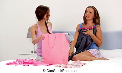 Girls looking at their shopping purchases at home on bed in...
