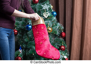 Girls looking for a gift in a Christmas sock near a decorated Christmas tree. Santa Claus brought new year holidays and gifts to loved ones.