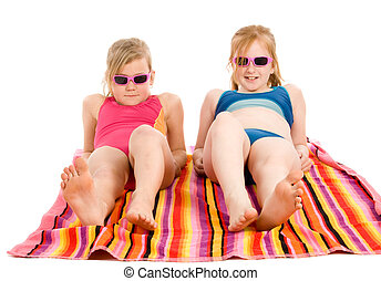 Girls lying on a towel - Two young girls lying together on a...