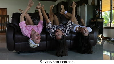 Girls Lying On Couch Upside Down Laughig Cheerful Living Room In Modern Apartment, Women Group Morning