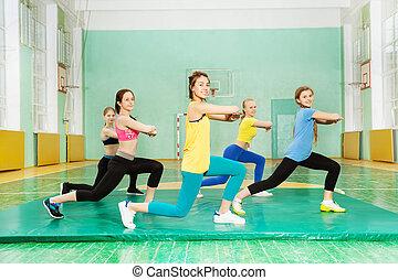 Girls making long step forward in sports hall