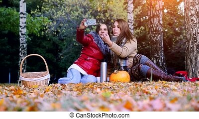 Girls making selfie on a picnic in autumn park sitting the fallen leaves near the pumpkin at halloween time. 3840x2160