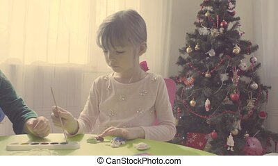 Girls near christmas tree painting ceramic toys
