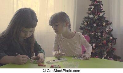 Girls near christmas tree painting ceramic toys - Girls near...