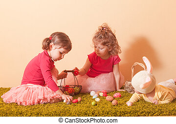 Girls on an Easter Egg hunt - Kids gather colorful eggs to...