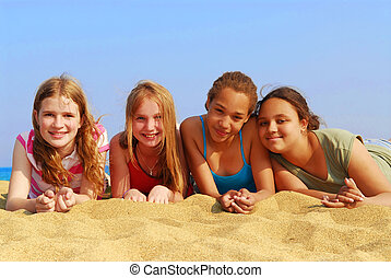 Girls on beach - Portrait of four smiling teenage girls on a...