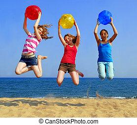 Girls on beach - Three girls with colorful beach balls ...