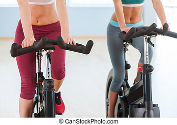 Girls on exercise bikes. Cropped image of two young women in sports clothing exercising on gym bicycles