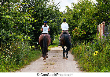 girls on horseback riding a country road back view