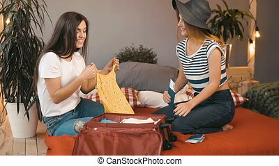 Girls Pack Suitcase for Trip - Good-looking caucasian girls...