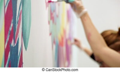 Girls painting brushes and paints on the wall. Slow motion.