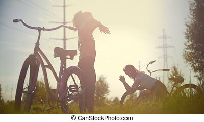 Girls perform exercises before walking on bicycles in the woods against the background of the sun