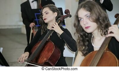 Girls play on violoncello in orchestra and contrabass...
