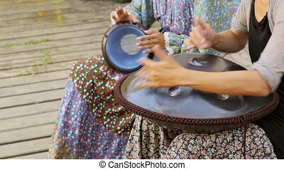 Girls play percussion instruments. Playing music on a djembe and tank drum. 4K