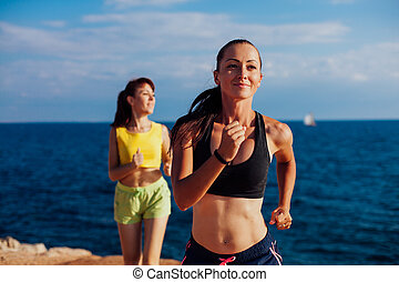 girls play sports jog on the beach