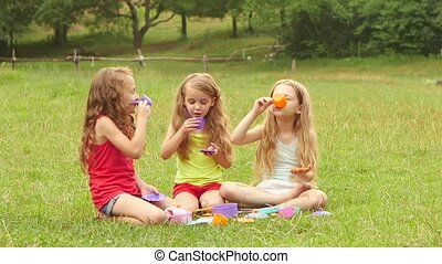 Girls play with toys, drinking tea and smiling outdoors. Slow motion