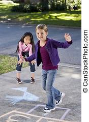 Girls playing hopscotch - Multiracial friends having fun...