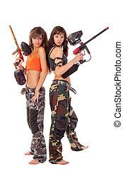 Girls playing paintball - Two young beautiful girls posing...