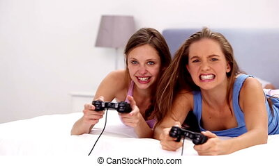 Girls playing video games on bed at girls night in