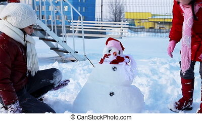 girls playing with snowman
