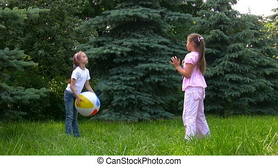 girls plays with ball in park with conifers - two happy...