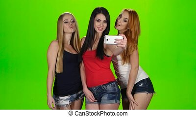 Girls pose for the camera of the smartphone. Green screen