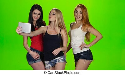 Girls pose for the camera of the tablet. Green screen