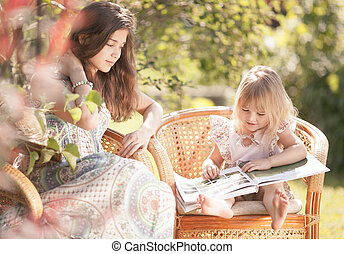 Girls reading book outdoor in summer day. Retro stylized.