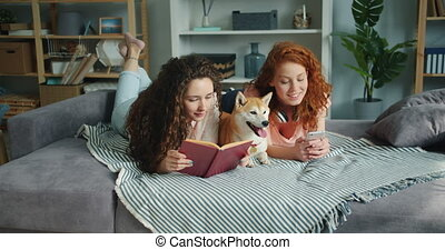 Girls reading book using smartphone lying on bed with dog in...