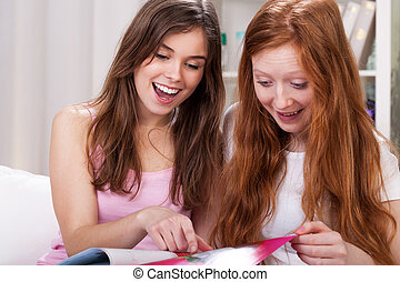 Girls reading magazines - Young girls reading magazines for...