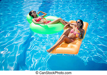Girls resting on air mattress in swimming pool - Two happy...